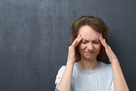 Portrait of unhappy caucasian fair-haired girl with closed eyes, touching temples with hands, suffering from migraine or thinking about unpleasant things, over gray background, copy space on left Stok Fotoğraf