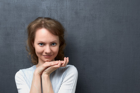 Studio portrait of smiling caucasian fair-haired girl, looking at camera, holding hands together under head, dreaming and being concentrated on pleasant thoughts, standing over gray background Stock Photo