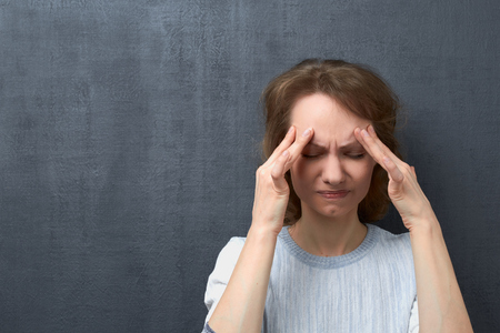 Portrait of unhappy caucasian fair-haired girl with closed eyes, touching forehead with hands, suffering from migraine or thinking about unpleasant things, over gray background, copy space on left Stok Fotoğraf