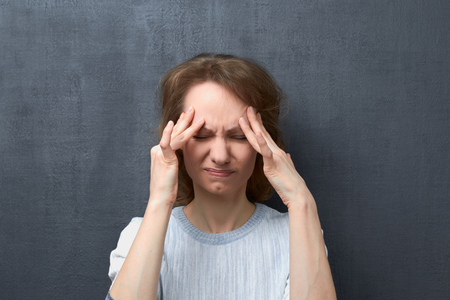 Portrait of unhappy and upset caucasian fair-haired young woman with closed eyes, touching forehead with hands, suffering from migraine or thinking about unpleasant things, over gray background