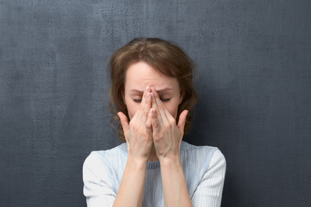 Studio portrait of unhappy and upset caucasian fair-haired young woman with closed eyes, covering face with hands, suffering from migraine or thinking about unpleasant things, over gray background Stock Photo