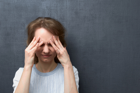 Portrait of upset caucasian fair-haired girl with closed eyes, touching forehead with hands, suffering from migraine or thinking about unpleasant things, over gray background, copy space on right