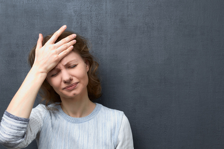 Portrait of upset caucasian fair-haired girl with closed eyes, holding one hand on forehead, suffering from headache or thinking about unpleasant things, over gray background, copy space on right Stok Fotoğraf