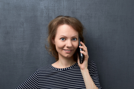 Studio close-up portrait of cute caucasian fair-haired girl, with surprised expression, smiling and looking at camera, talking about something interesting on phone, standing over gray background