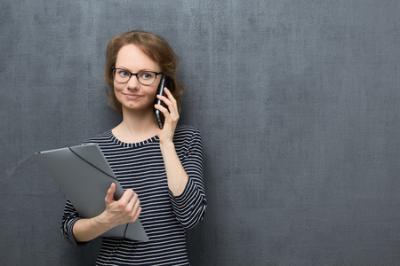 Studio portrait of cute caucasian fair-haired girl with glasses, wearing striped blouse, smiling and looking aside, talking on phone, holding folder in hand, over gray background, copy space on right