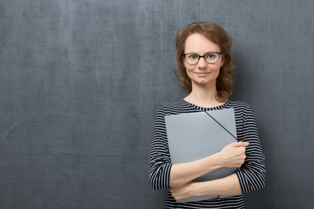 Studio portrait of happy caucasian fair-haired girl with eyeglasses, with striped blouse, smiling calmly and looking at camera, holding folder in hands, against gray background, copy space on left Stock Photo