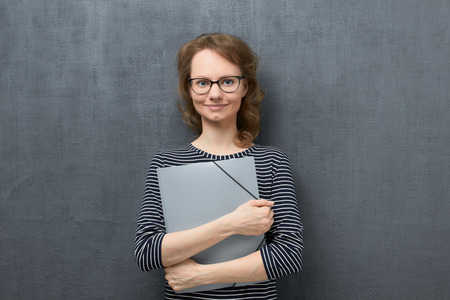 Studio waist-up portrait of happy caucasian fair-haired girl with eyeglasses, in striped blouse, smiling calmly and looking at camera, holding folder in hands, standing against gray background