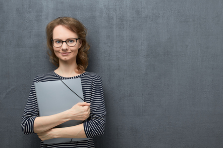Studio portrait of happy caucasian fair-haired young woman with glasses, in striped blouse, smiling calmly and looking at camera, holding folder in hands, over gray background, copy space on right