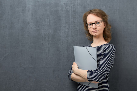 Studio waist-up portrait of calm caucasian fair-haired young woman with glasses, smiling slightly and looking at camera, holding folder in hands, against gray background, copy space on left