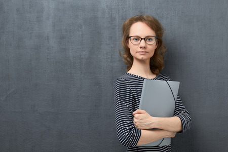 Studio waist-up portrait of calm caucasian fair-haired young woman with eyeglasses, smiling slightly and looking at camera, holding folder in hands, against gray background, copy space on left Stock Photo