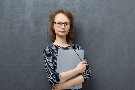 Studio waist-up portrait of calm caucasian fair-haired girl with eyeglasses, wearing striped blouse, smiling slightly and looking at camera, holding folder in hands, standing against gray background