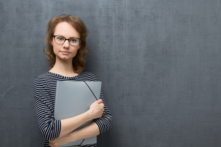 Studio portrait of calm caucasian fair-haired young woman with glasses, wearing striped blouse, smiling and looking at camera, holding folder in hands, over gray background, copy space on right