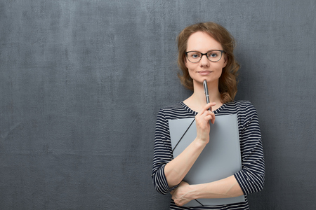 Studio waist-up portrait of calm caucasian fair-haired young woman with eyeglasses, smiling slightly and looking at camera, holding folder and pen in hands, against gray background, copy space on left