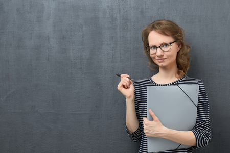 Studio waist-up portrait of pleased caucasian fair-haired young woman with eyeglasses, smiling and looking at camera, holding folder and pen in hands, against gray background, copy space on left