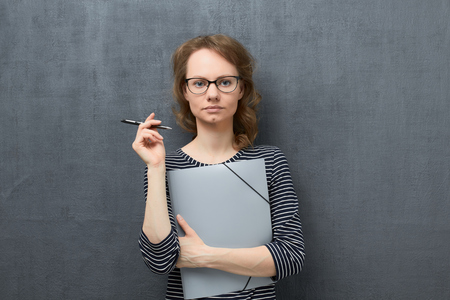 Studio portrait of serious caucasian fair-haired young woman with glasses, wearing striped blouse, looking at camera with strict expression, holding folder and pen in hands, over gray background Stock Photo