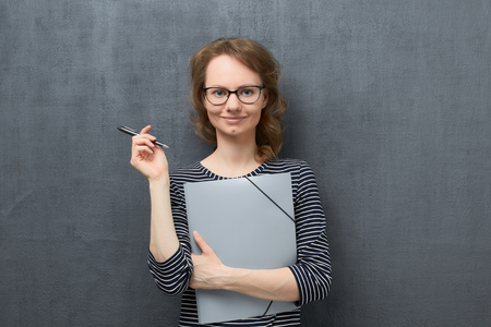 Studio waist-up portrait of pleased caucasian fair-haired girl with eyeglasses, wearing striped blouse, smiling and looking at camera, holding folder and pen in hands, against gray background