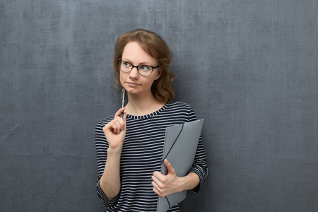 Studio portrait of pensive caucasian fair-haired young woman with glasses, wearing striped blouse, looking aside, thinking and making choice, holding folder and pen in hands, over gray background