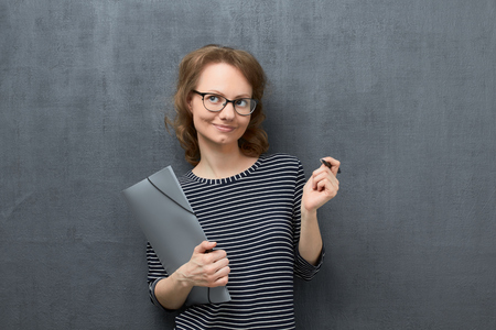 Studio portrait of dreaming caucasian fair-haired girl with eyeglasses, wearing striped blouse, looking aside, concentrated on pleasant thoughts, holding folder and pen in hands, over gray background