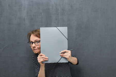 Studio waist-up portrait of afraid caucasian fair-haired young woman with eyeglasses, in striped blouse, looking with curiosity out from folder, hiding behind folder, against gray background Stock Photo