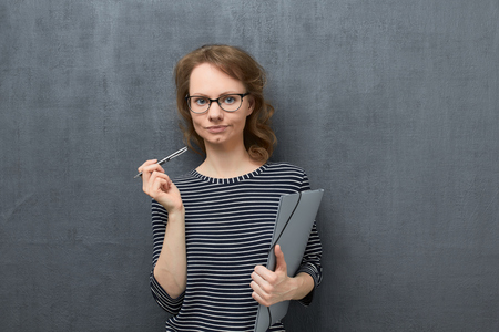 Studio waist-up portrait of dissatisfied caucasian fair-haired young woman with glasses, wearing striped blouse, looking at camera, holding folder and pen in hands, standing over gray background