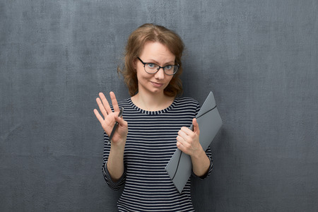 Studio portrait of confident caucasian fair-haired woman with glasses, wearing striped blouse, looking at camera, holding folder and pen in hands, over gray background, no need to worry, all is ok