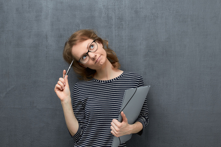 Studio portrait of pensive caucasian fair-haired girl with glasses, wearing striped blouse, looking dreamily aside, thinking and making choice, holding folder and pen in hands, over gray background