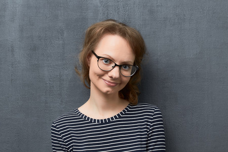 Studio close-up portrait of cute caucasian fair-haired girl with glasses, wearing striped blouse, tilting head, smiling romantically, flirting and looking at camera, standing against gray background
