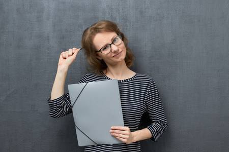 Studio waist-up portrait of thoughtful caucasian fair-haired girl with eyeglasses, looking at camera, thinking and making difficult choice, holding folder and pen in hands, over gray background
