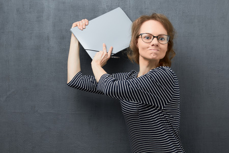 Studio portrait of angry caucasian fair-haired young woman with glasses, with frowning face, looking with hatred, swinging folder and trying to hit somebody, over gray background