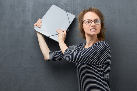 Studio waist-up portrait of angry caucasian fair-haired girl with eyeglasses, frowning face, looking with hatred, clenching teeth, swinging folder and trying to hit somebody, over gray background