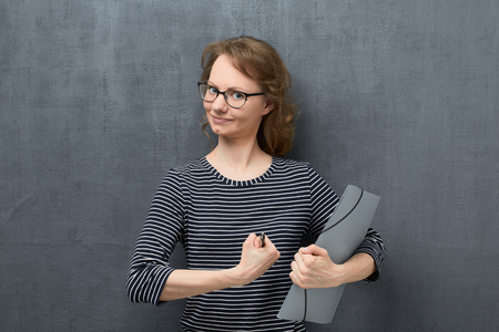 Portrait of vigorous caucasian fair-haired girl with glasses, wearing striped blouse, looking enthusiastically at camera, being full of energy to work, folder and pen in hands, over gray background Banco de Imagens