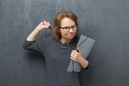 Studio portrait of angry caucasian fair-haired young woman with glasses, with frowning face, looking at camera, holding folder and pen in hands, swinging with fist, over gray background