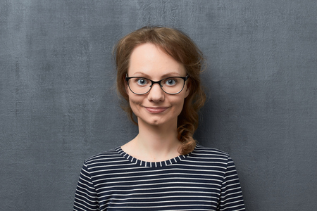 Studio close-up portrait of cute caucasian fair-haired girl with eyeglasses, wearing striped blouse, smiling romantically, looking at camera, standing against gray background