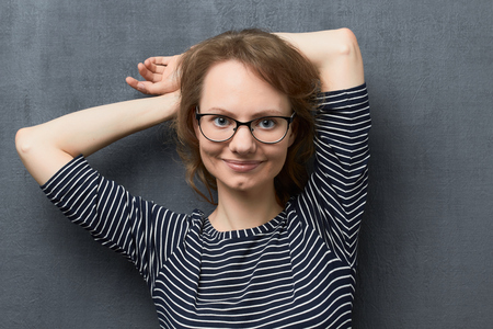 Studio portrait of cute caucasian fair-haired girl with eyeglasses, wearing striped blouse, smiling broadly and looking at camera, holding hands folded behind head, standing against gray background