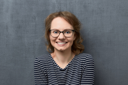 Studio close-up portrait of cute caucasian fair-haired young woman with eyeglasses, wearing striped blouse, smiling broadly with teeth, looking at camera, raising shoulders, against gray background