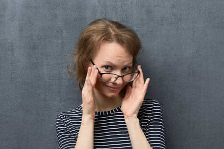 Studio portrait of cute caucasian fair-haired girl with eyeglasses, wearing striped blouse, smiling and looking over top of glasses at camera, holding glasses frames with hands, over gray background Stock Photo