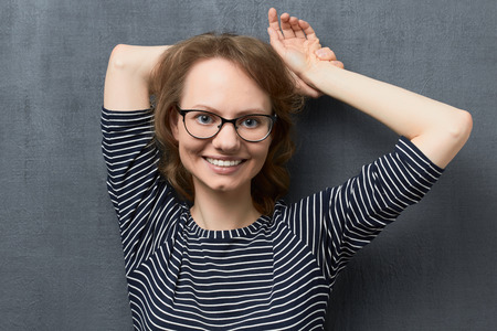 Studio portrait of cute caucasian fair-haired girl with eyeglasses, wearing striped blouse, smiling broadly with teeth and looking at camera, holding hands folded behind head, against gray background 스톡 콘텐츠