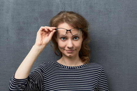 Studio close-up portrait of cute caucasian fair-haired girl with glasses, smiling and looking with interest from under glasses at camera, holding glasses frames with one hand, against gray background