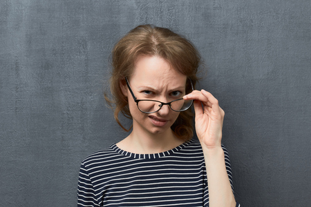 Studio close-up portrait of discontent caucasian fair-haired girl, holding glasses frames with one hand, looking contemptuously over top of glasses at camera, frowning face, against gray background Reklamní fotografie