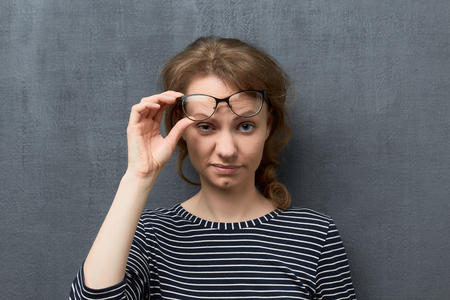 Studio portrait of discontent caucasian fair-haired young woman with eyeglasses on forehead, holding glasses frames with one hand, looking contemptuously at camera, against gray background