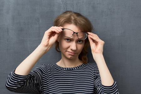 Studio portrait of discontent caucasian fair-haired girl with eyeglasses, looking with suspicion and doubt from under glasses at camera, holding glasses frames with hands, against gray background