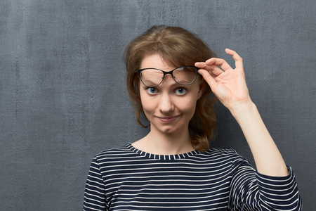 Studio close-up portrait of cute caucasian fair-haired young woman with glasses, smiling and looking with interest from under glasses at camera, holding glasses frames with hand, over gray background Stock Photo