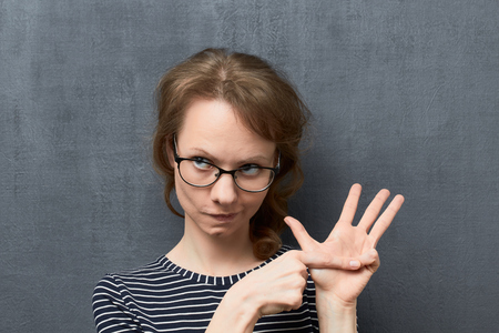 Studio close-up portrait of concentrated caucasian fair-haired girl with glasses, looking thoughtfully aside, counting of something with fingers, against gray background, the first counted item Reklamní fotografie