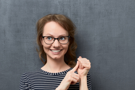 Studio close-up portrait of pleased caucasian fair-haired young woman with glasses, smiling broadly looking aside, making list of something with fingers, over gray background, the fifth listed item