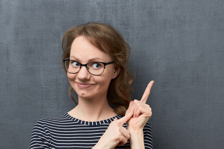 Studio close-up portrait of caucasian fair-haired young woman with eyeglasses, smiling broadly and looking aside, counting of something with fingers, against gray background, the fourth counted item