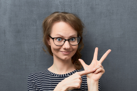 Studio close-up portrait of caucasian fair-haired girl with glasses, smiling and looking at camera, folding fingers while counting of something, against gray background, the second counted item Reklamní fotografie