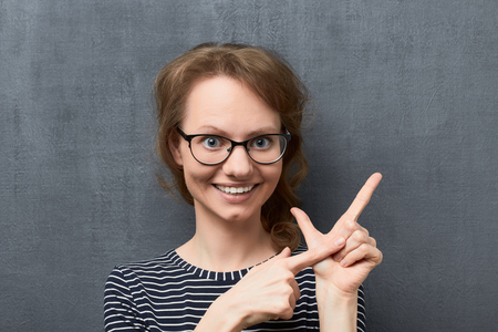 Studio close-up portrait of caucasian fair-haired girl with glasses, smiling broadly and looking at camera, counting of something with fingers, against gray background, the third counted item Reklamní fotografie
