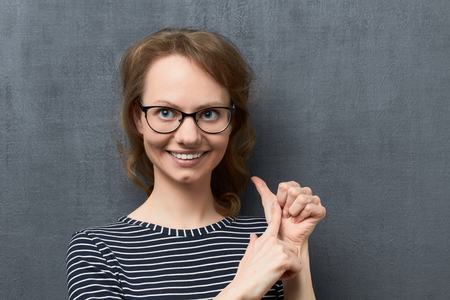 Studio close-up portrait of pleased caucasian fair-haired young woman with glasses, smiling and looking aside, making list of something with fingers, over gray background, the fourth listed item