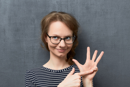 Studio close-up portrait of pleased caucasian fair-haired young woman with glasses, smiling and looking aside, making list of something with fingers, over gray background, the first listed item