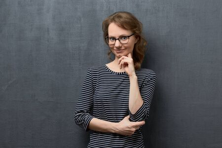 Studio waist-up portrait of thoughtful caucasian fair-haired girl with eyeglasses, wearing striped blouse, smiling and looking at camera, holding hand near chin, standing over gray background Banco de Imagens
